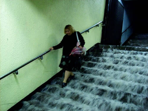 woman walking down flooded stairs
